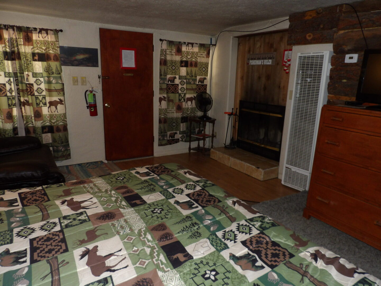 bedroom with electric fan, heating, and fireplace