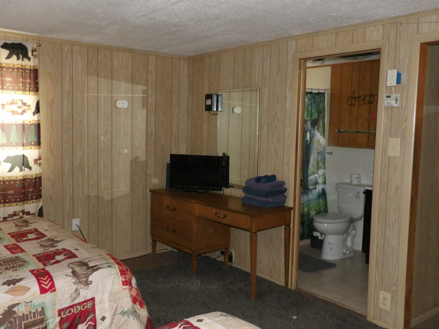 bedroom table with TV and entrance to bathroom